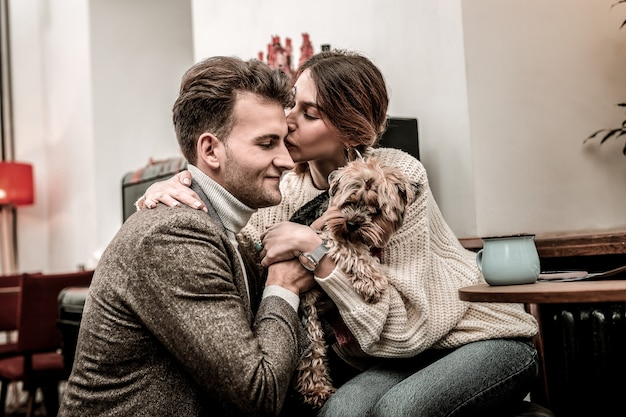 Wdzięczność za prezent. wdzięczna kobieta całuje swojego partnera, trzymając psa