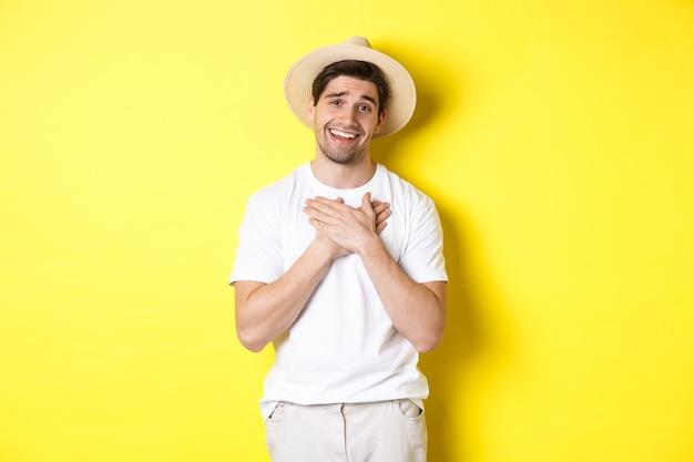 Wdzięczny facet w słomkowym kapeluszu trzymający ręce na sercu, mówiący dziękuję i uśmiechający się z wdzięcznością, stojący przed żółtą ścianą