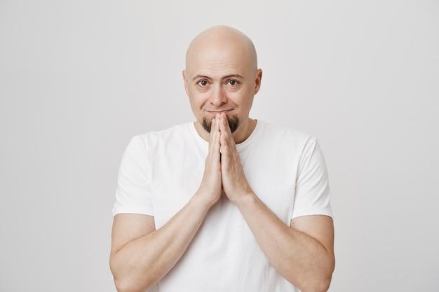 Wdzięczny i pełen nadziei łysy mężczyzna w średnim wieku trzyma się za ręce w modlitwie