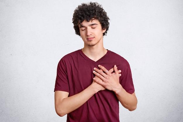 Wdzięczny młody chłopak trzyma ręce na sercu, będąc wzruszony historią przeszywającą serce, trzyma oczy zamknięte, nosi swobodny strój