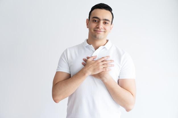 Wdzięczny młody człowiek utrzymuje ręki na klatce piersiowej i patrzeje kamerę.