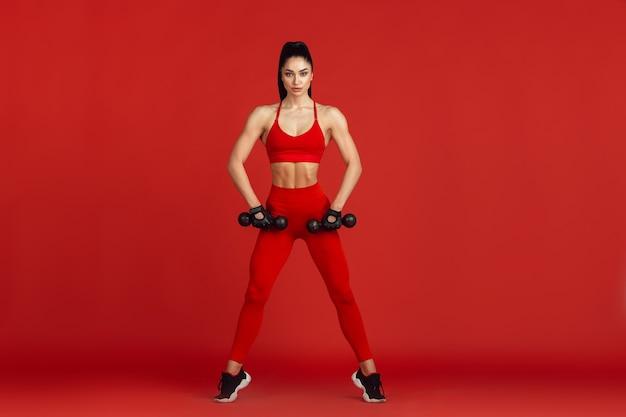 Wdzięczny. piękna młoda kobieta lekkoatletka praktykuje w studio, portret monochromatyczny czerwony.