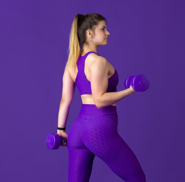 Wdzięczny. piękna młoda lekkoatletka praktykujących, monochromatyczny fioletowy portret. sportowy krój kaukaski model z ciężarkami. koncepcja budowy ciała, zdrowego stylu życia, piękna i działania.