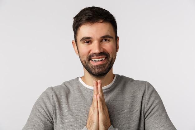 Wdzięczny zadowolony przystojny brodaty mężczyzna wyraża wdzięczność i przyjemność spotkać się z kimś, pokłonić się grzecznie zaciśniętymi dłońmi, wykonać gest modlitwy dziękując za pomoc, uśmiechając się zadowolony