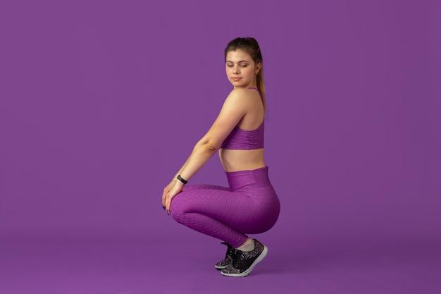 Wdzięk. piękna młoda kobieta lekkoatletka praktykuje w studio, portret monochromatyczny fioletowy.