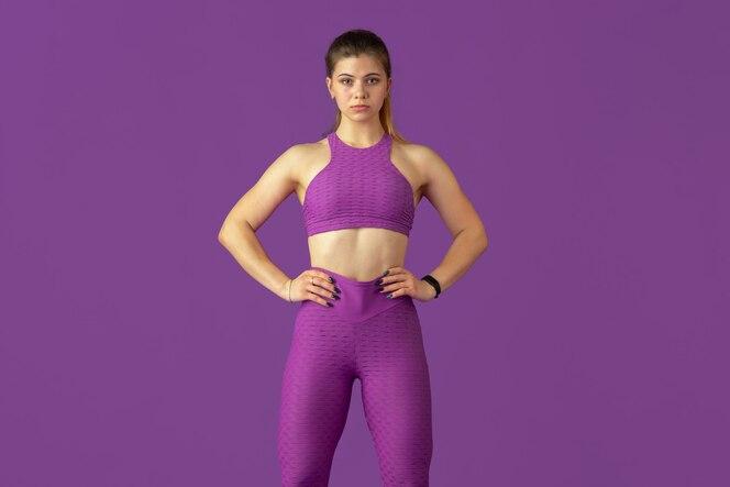 Wdzięk. piękna młoda lekkoatletka praktykujących w, monochromatyczny fioletowy portret. sportowy model kaukaski pozowanie pewnie. koncepcja budowy ciała, zdrowego stylu życia, piękna i działania.