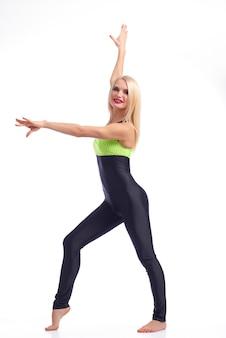 Wdzięk sportowego. pełne ujęcie pięknej blondynki gimnastyczki uśmiechającej się radośnie pozującej w dopasowanym dresie na białym tle
