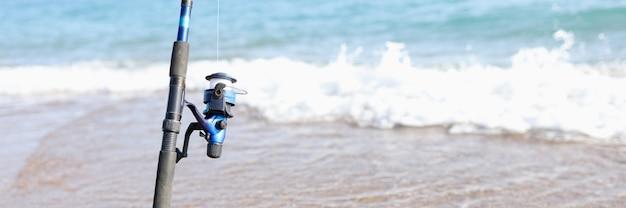 Wędka do połowu ryb stoi na wybrzeżu morza