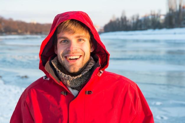Wędkarstwo podlodowe to zimowa tradycja. mężczyzna ciepła kurtka jasne tło stałe lodu. eksploracja regionów polarnych. zimowe miejsca docelowe. środki bezpieczeństwa. odkrywca polarny. zimowa odzież męska. zimowy strój.