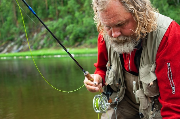Wędkarz na muchę sprawia, że rzuca się stojąc w wodzie