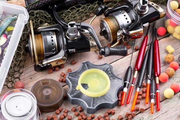 Wędki i spinningi w kompozycji z akcesoriami do łowienia na starej powierzchni na stole