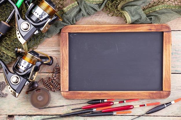 Wędki, tablica i spinningi w kompozycji z akcesoriami do łowienia na starej powierzchni na stole
