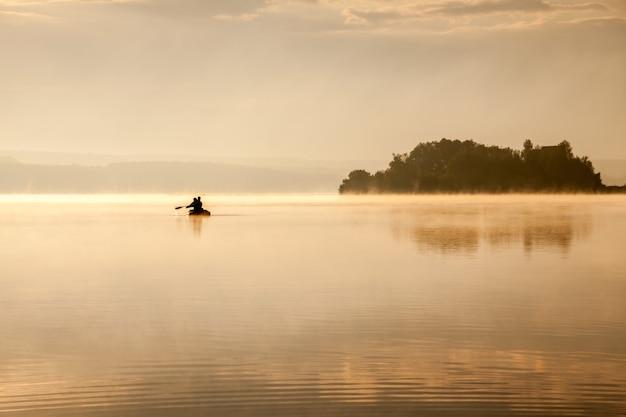 Wędkowanie na jeziorze rano o wschodzie słońca