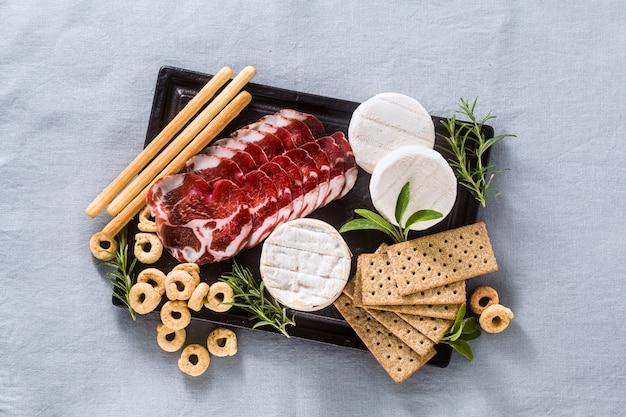 Wędliny i ser podawane są na tacy na stole z białym winem, krakersami, grissini i taralli z aromatycznymi ziołami na niebieskim lnianym obrusie.
