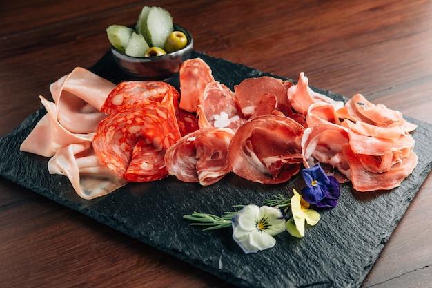 Wędliny na kamiennym talerzu z prosciutto, bekonem, salami i kiełbaskami.