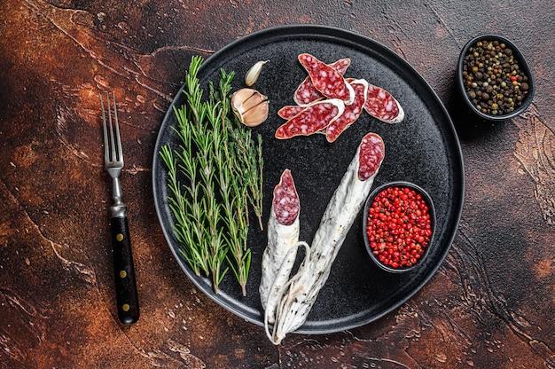 Wędliny z kiełbasą fuet salami i rozmarynem na talerzu.