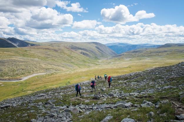 Wędrowcy w górach, ekipa turystów z plecakami idąca po górskim szlaku, letni wypoczynek i zajęcia sportowe