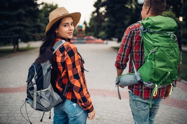 Wędrowcy z plecakami podróżujący po miejscowości turystycznej