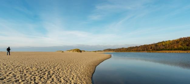 Wędrowiec idzie wzdłuż piaszczystej plaży w kierunku wydm w yantarny w rosji.