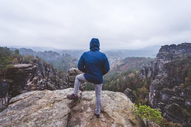 Wędrowiec w plenerowej wycieczce górskiej na szczyt góry, z widokiem na grzbiet na horyzoncie