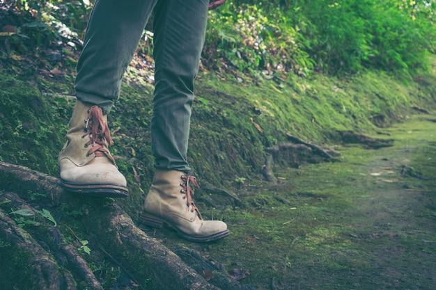 Wędrówki koncepcji - bliska męskich nóg na leśnej drodze