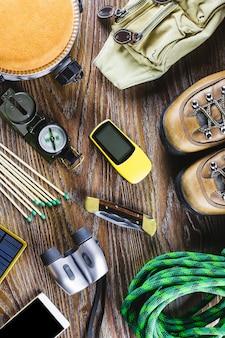 Wędrówki lub podróży sprzęt z butami, kompas, lornetki, mecze na drewniane tła. koncepcja aktywnego stylu życia