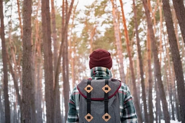 Wędrówki mężczyzna w zimowym lesie. mężczyzna w kraciastej koszuli zimowej spaceru w pięknym lesie snowy