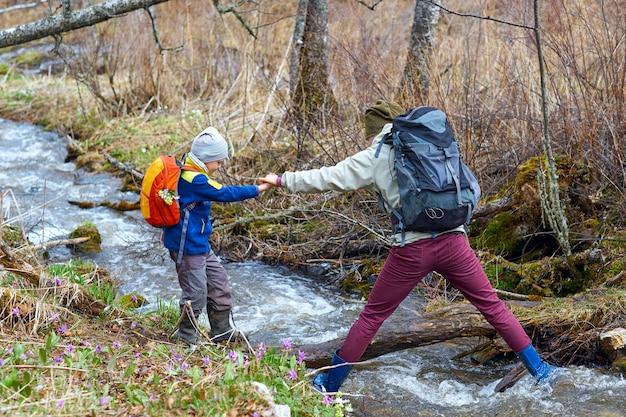 Wędrująca matka pomaga synowi przekroczyć górski potok, trzyma go za rękę. sportowa rodzina z plecakami