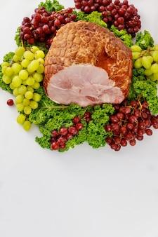 Wędzona cała szynka wieprzowa ze świeżymi owocami. zdrowe jedzenie. posiłek wielkanocny.
