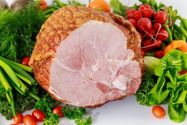 Wędzona cała szynka ze zdrowymi świeżymi warzywami.