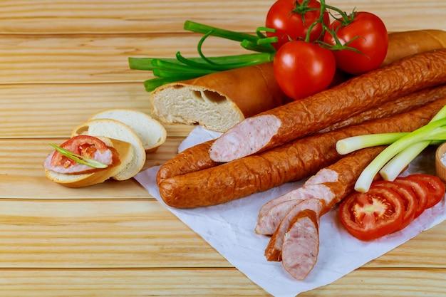 Wędzona kiełbasa europejska na drewnianym stole z pomidorem, pieczywem i szczypiorkiem