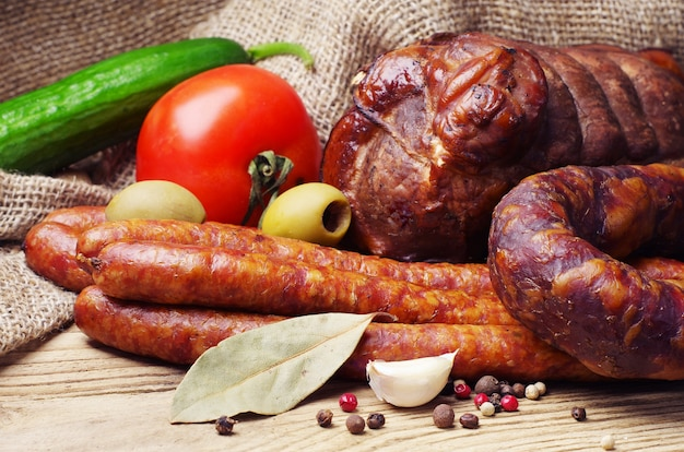 Wędzona kiełbasa, mięso i warzywa na drewnianym stole