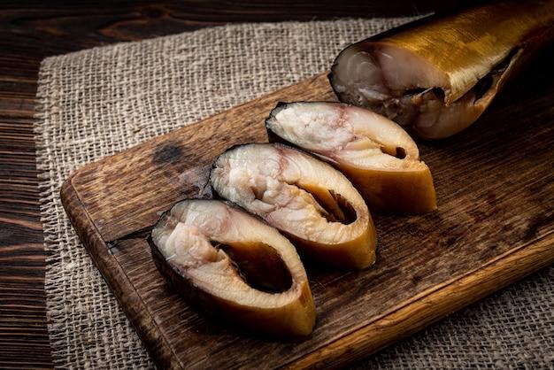 Wędzona makrela na desce na ciemnym drewnianym stole.