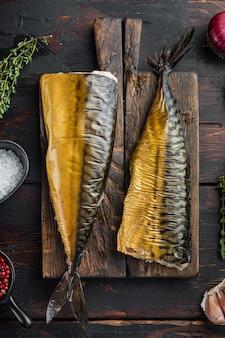 Wędzona makrela rybna, na starym ciemnym tle drewnianego stołu, widok z góry płaski lay