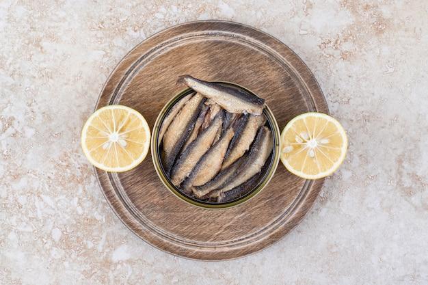 Wędzona mała rybka w misce z plasterkami cytryny