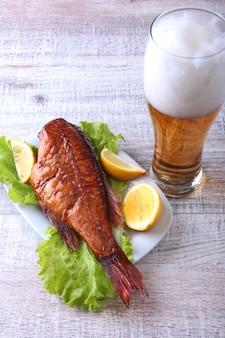 Wędzona ryba i cytryna na zielonej sałacie opuszczają na drewnianej tnącej desce i szkle z piwem na bielu