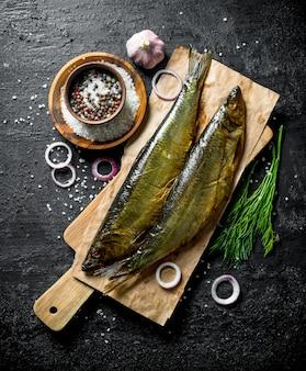 Wędzona ryba z koperkiem, przyprawami i cebulą. na czarnym rustykalnym