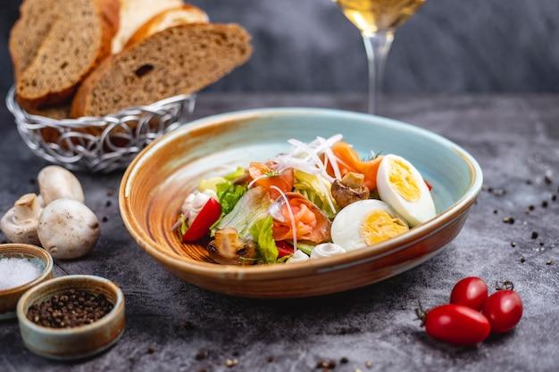 Wędzona sałatka z łososia z gotowaną jajkiem, pomidorową sałatą, grzybową cebulą