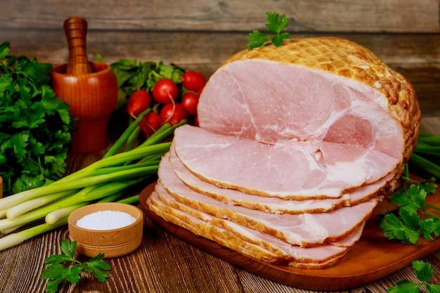 Wędzona szynka bez kości z warzywami i solą na drewnianym stole.