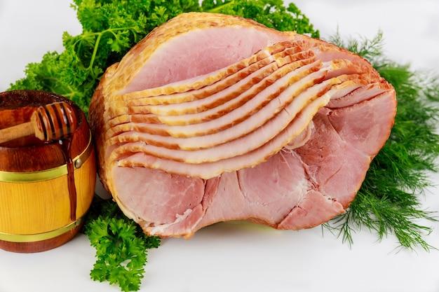 Wędzona szynka wieprzowa w plastrach z miodem w drewnianym słoju.
