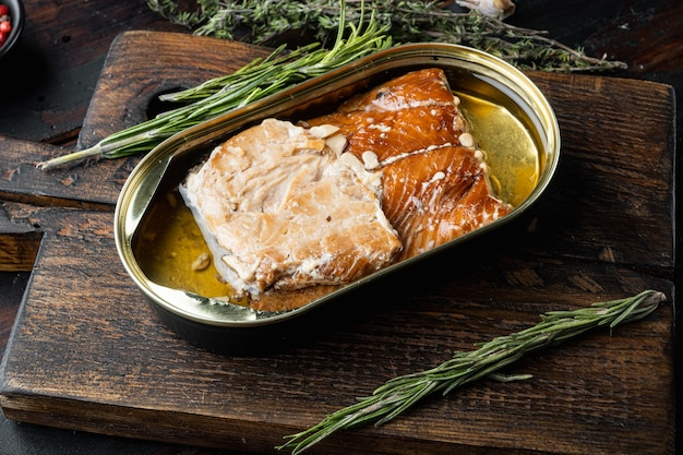 Wędzone filety z łososia konserwy rybne, na drewnianej desce do krojenia, na starym ciemnym drewnianym stole z ziołami i dodatkami