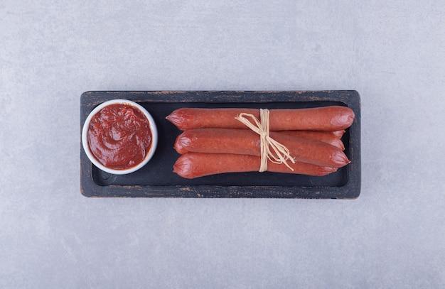 Wędzone kiełbaski i ketchup na ciemnym talerzu.