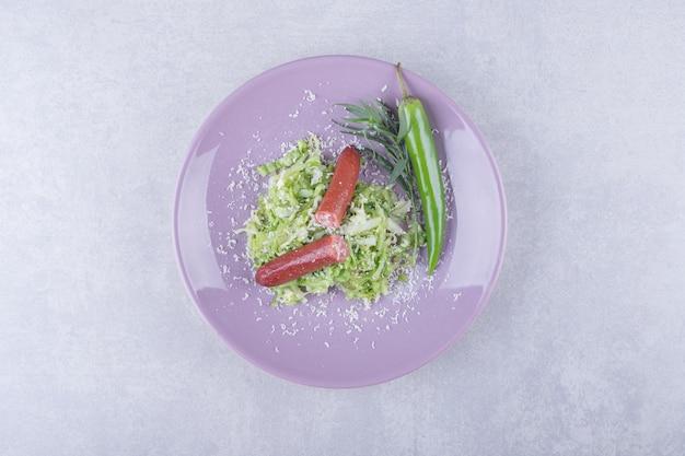 Wędzone kiełbaski i papryczka chili na fioletowym talerzu.