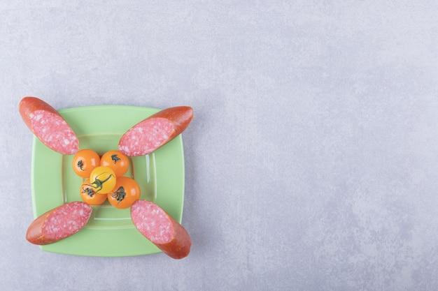 Wędzone kiełbaski i pomidorki koktajlowe na zielonym talerzu.