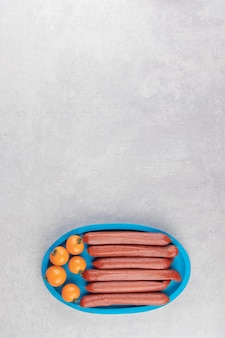 Wędzone kiełbaski i pomidory na niebieskim talerzu.