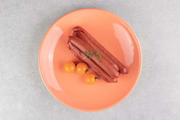 Wędzone kiełbaski i pomidory na pomarańczowym talerzu.