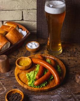 Wędzone kiełbaski podawane z sałatą, musztardą i piwem