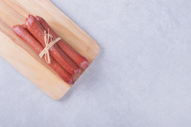 Wędzone kiełbaski przewiązane liną na desce.