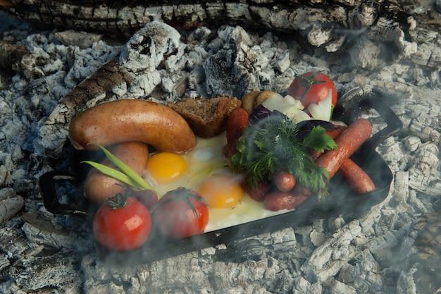 Wędzone kiełbaski z pomidorami i jajkami leżą na węglu drzewnym. danie gotowane i wędzone na węglu drzewnym