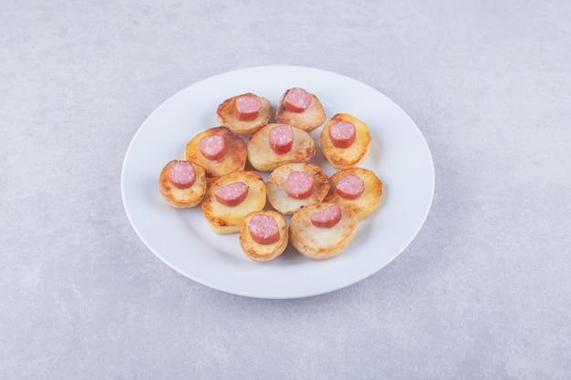 Wędzone kiełbaski ze smażonym ziemniakiem na białym talerzu.